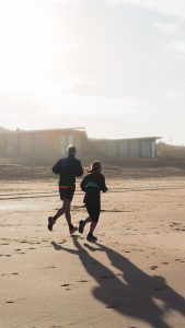 Two people running on beach.